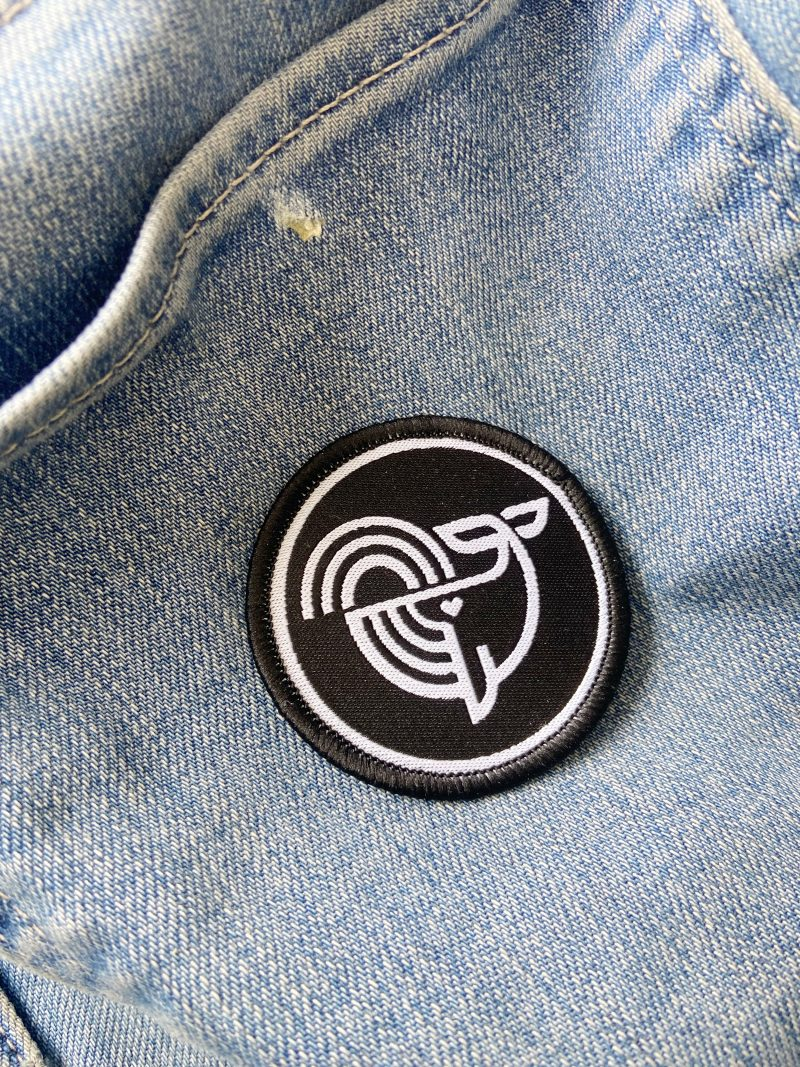 Embroidered Patch with Ecotribo Cleaning Seas icon on jeans